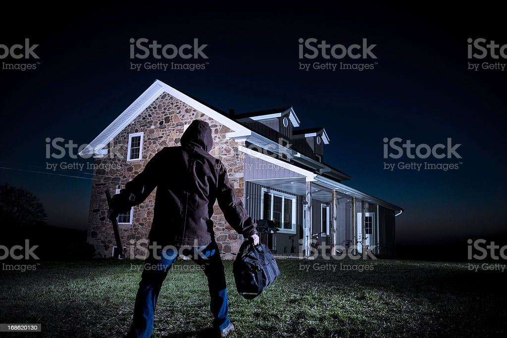 Burglar outside a house at night stock photo