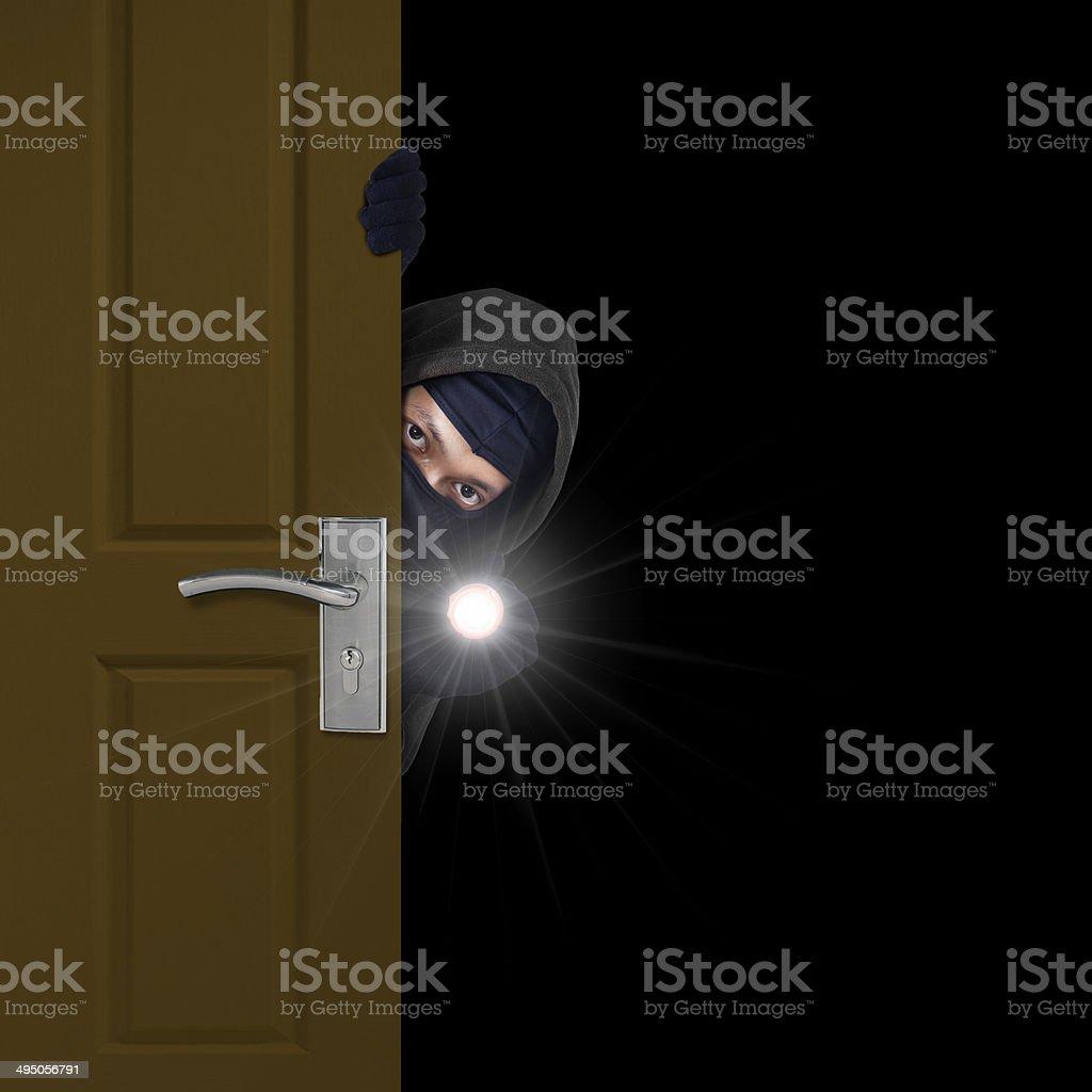 Burglar sneaking through door stock photo