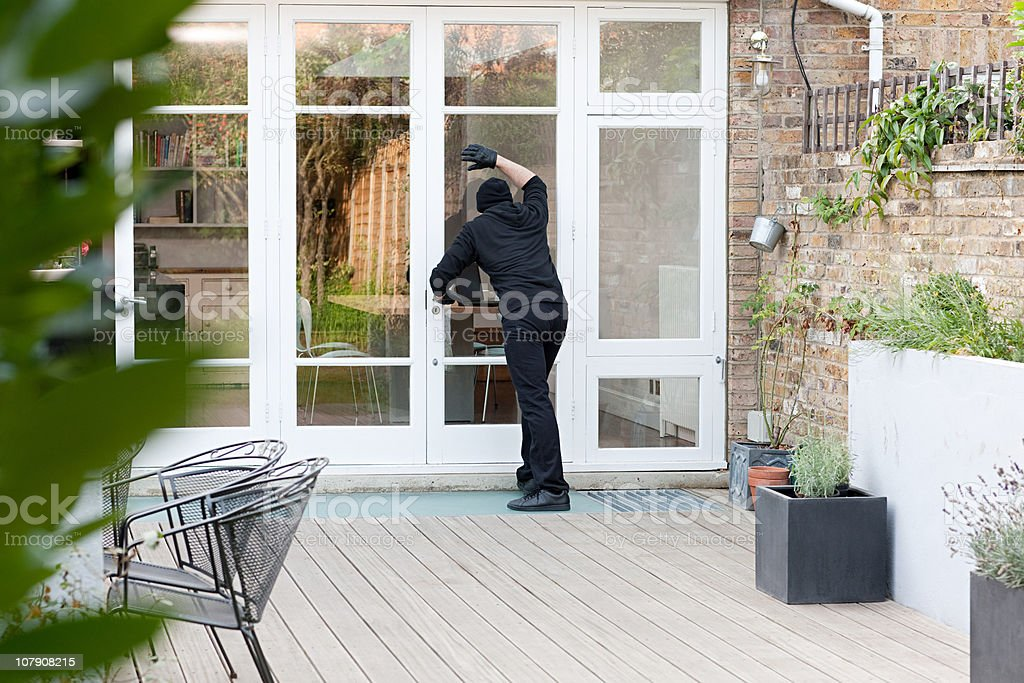 Burglar standing at patio door stock photo