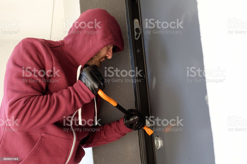 Burglar trying to force a door lock stock photo