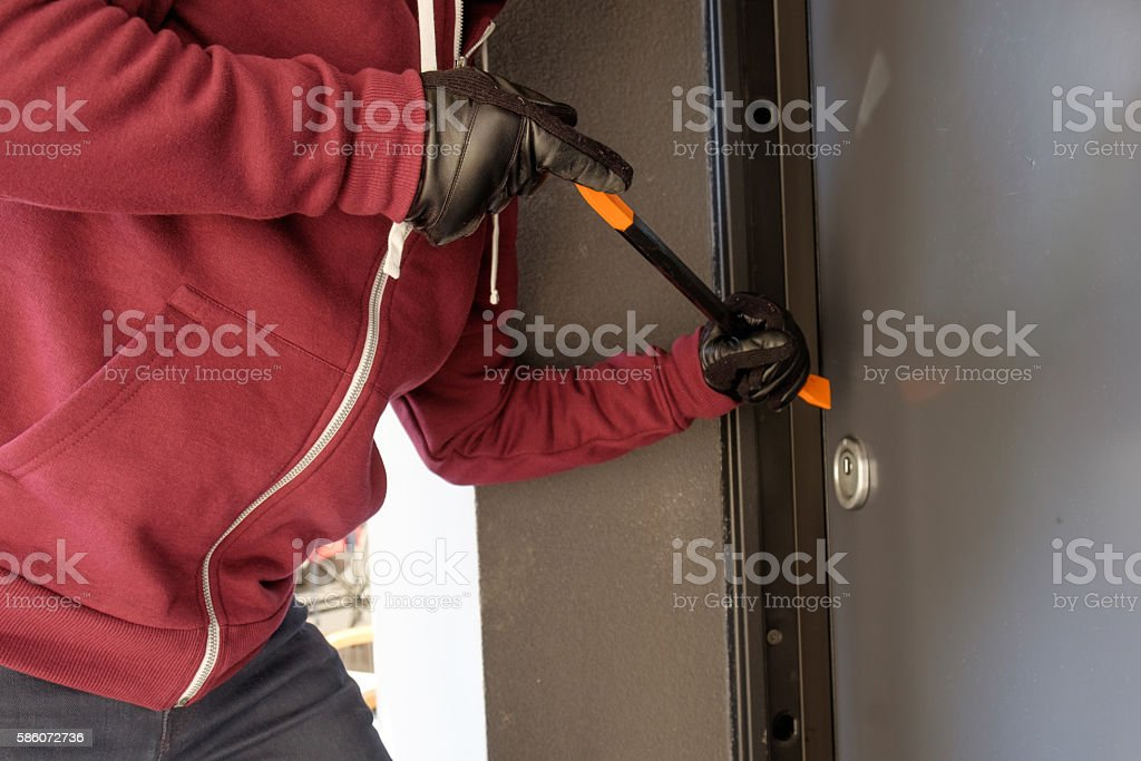 Burglar trying to force a door lock using a crowbar stock photo