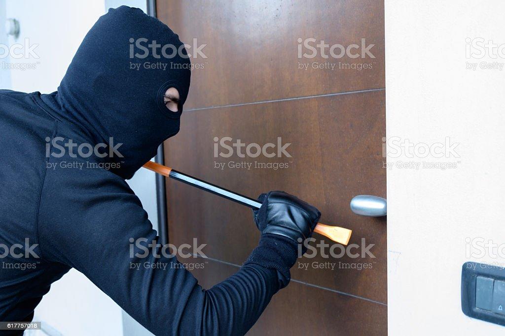 Burglar trying to force a door lock using a crowbar stock photo