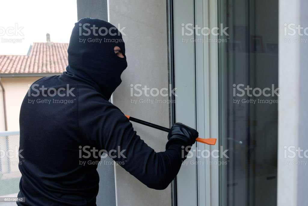 Burglar trying to force a door lock using crowbar stock photo
