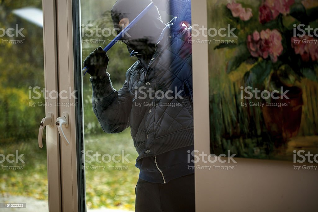 Burglar trying to open the window stock photo