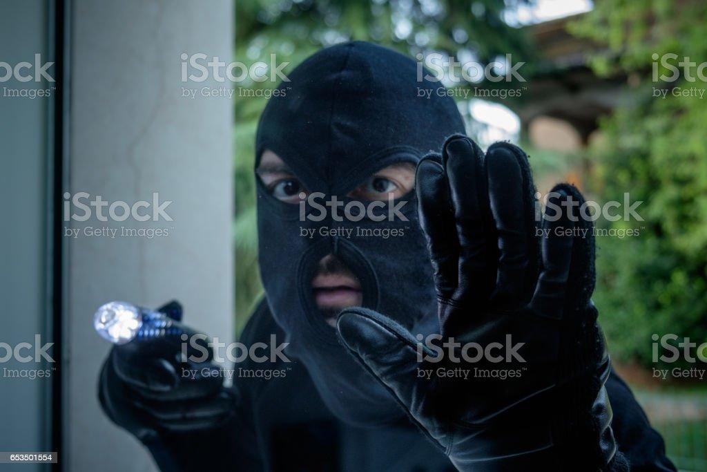 Burglar wearing a balaclava holding a flashlight stock photo