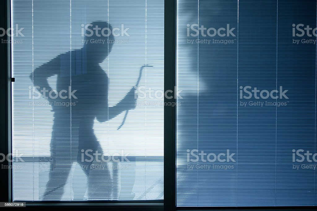 Burglar wearing a balaclava looking through the house window stock photo