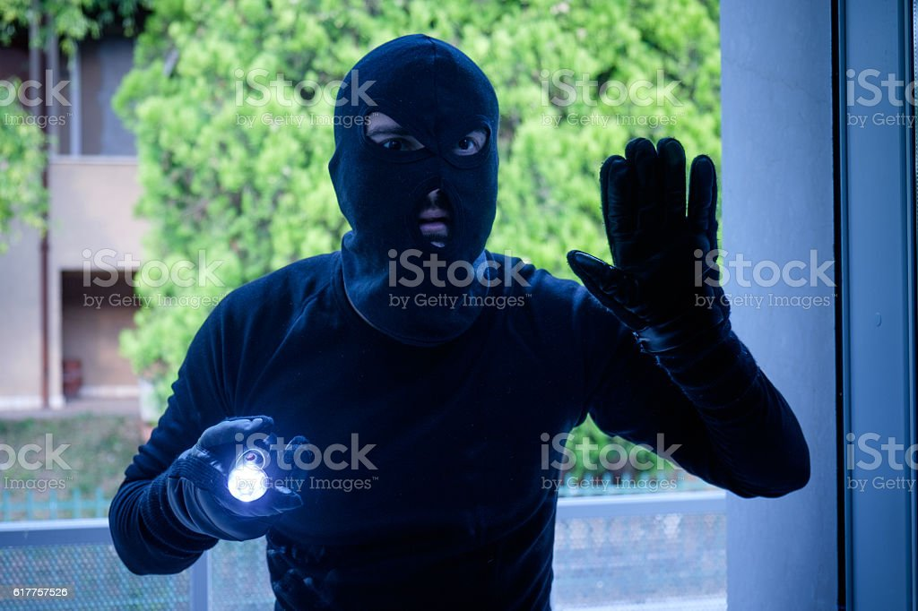 Burglar wearing a balaclava looking through the house window stock photo