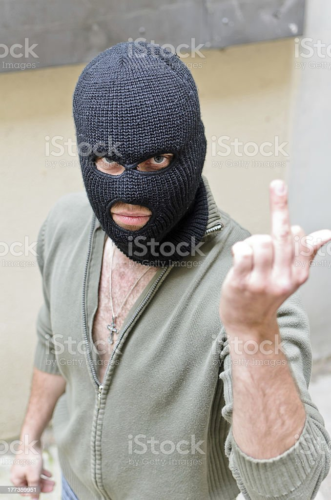 Burglar wearing a mask shows middle finger royalty-free stock photo