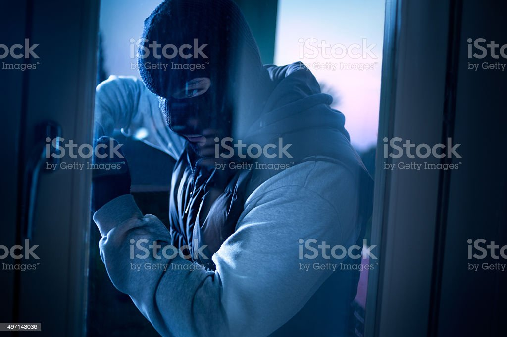 burglar with crowbar breaking into a house stock photo