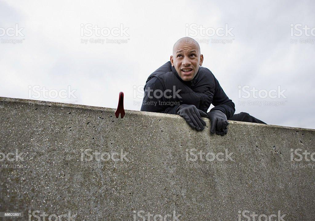 Burglar with crowbar climbing over wall royalty-free stock photo