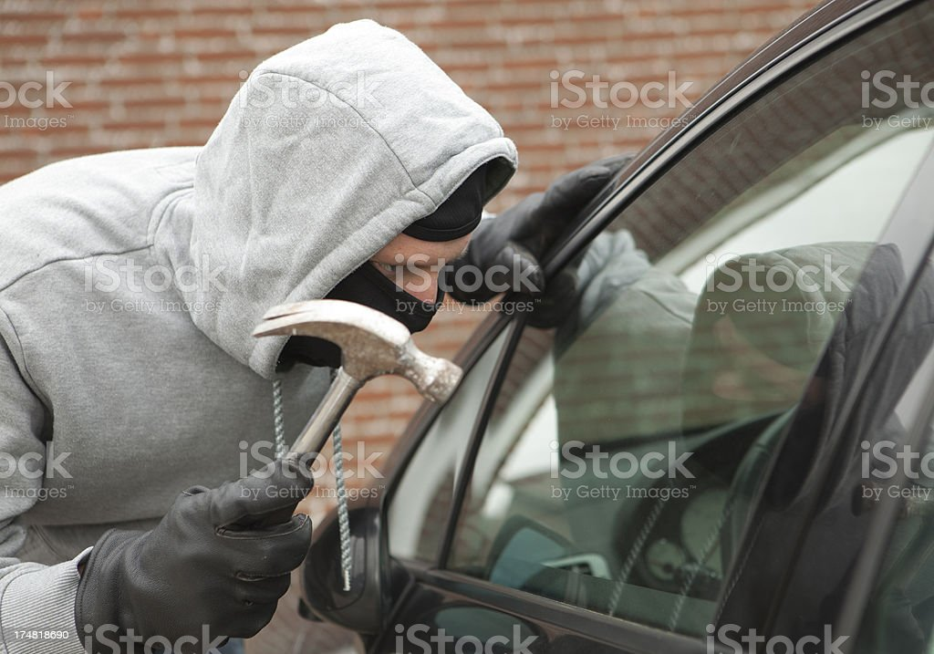 Burglar with crowbar trying to enter car, stealing valuables royalty-free stock photo