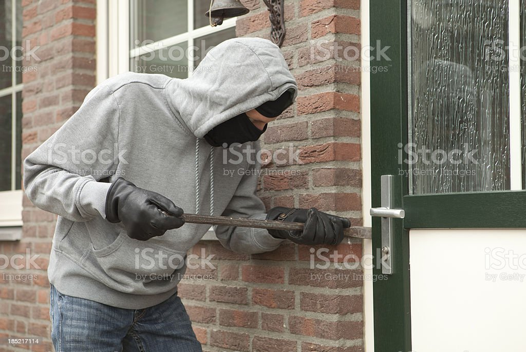 Burglar with crowbar trying to enter house, stealing valuables royalty-free stock photo