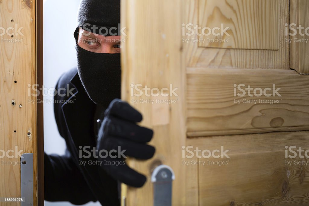 Burglary crime - burglar opening a door stock photo