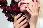 Burgundy manicure with gladiolus.