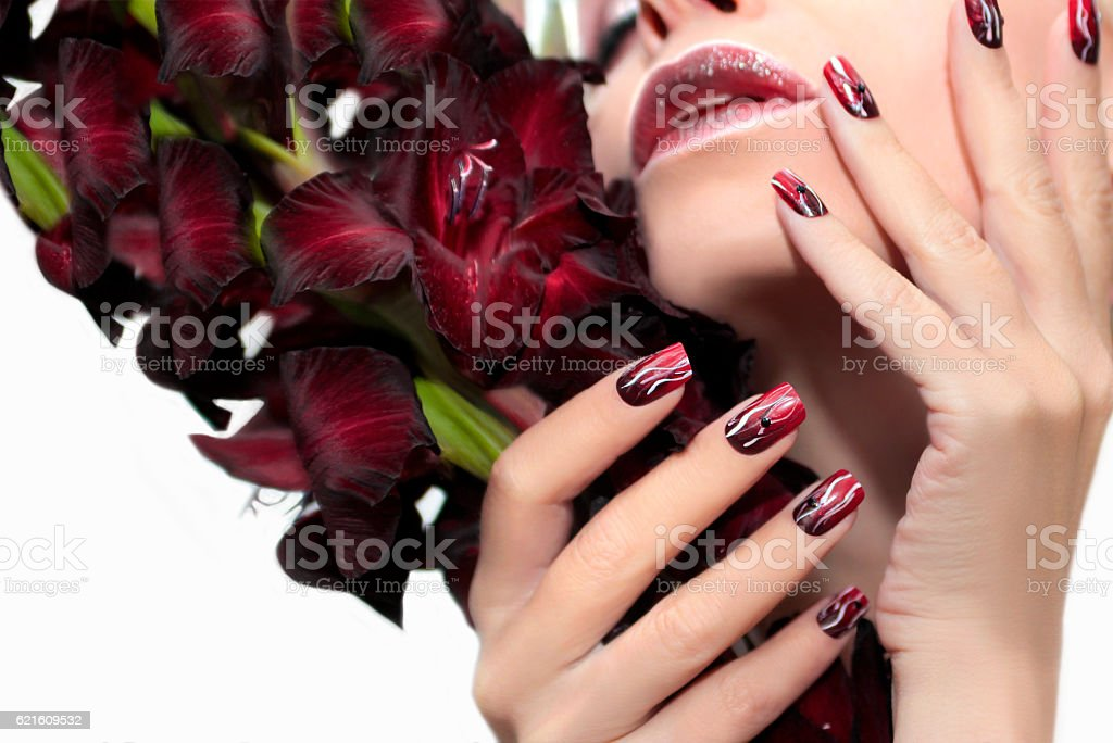 Burgundy manicure with gladiolus. stock photo
