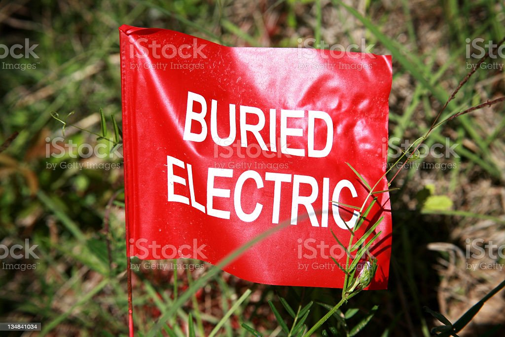 Buried electric cable flag staked in ground. Red. royalty-free stock photo