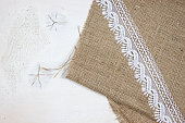 Burlap and lace on white wood background