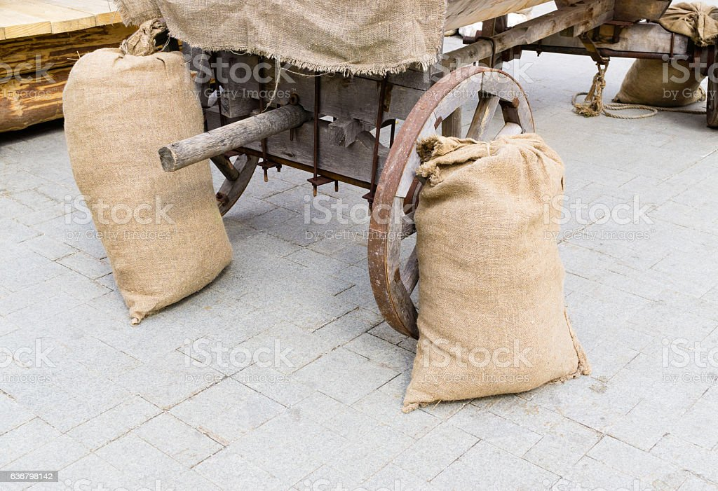 Burlap sacks near cart stock photo