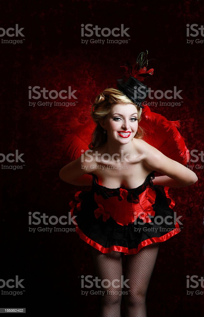 Burlesque woman in red holding feather fan stock photo