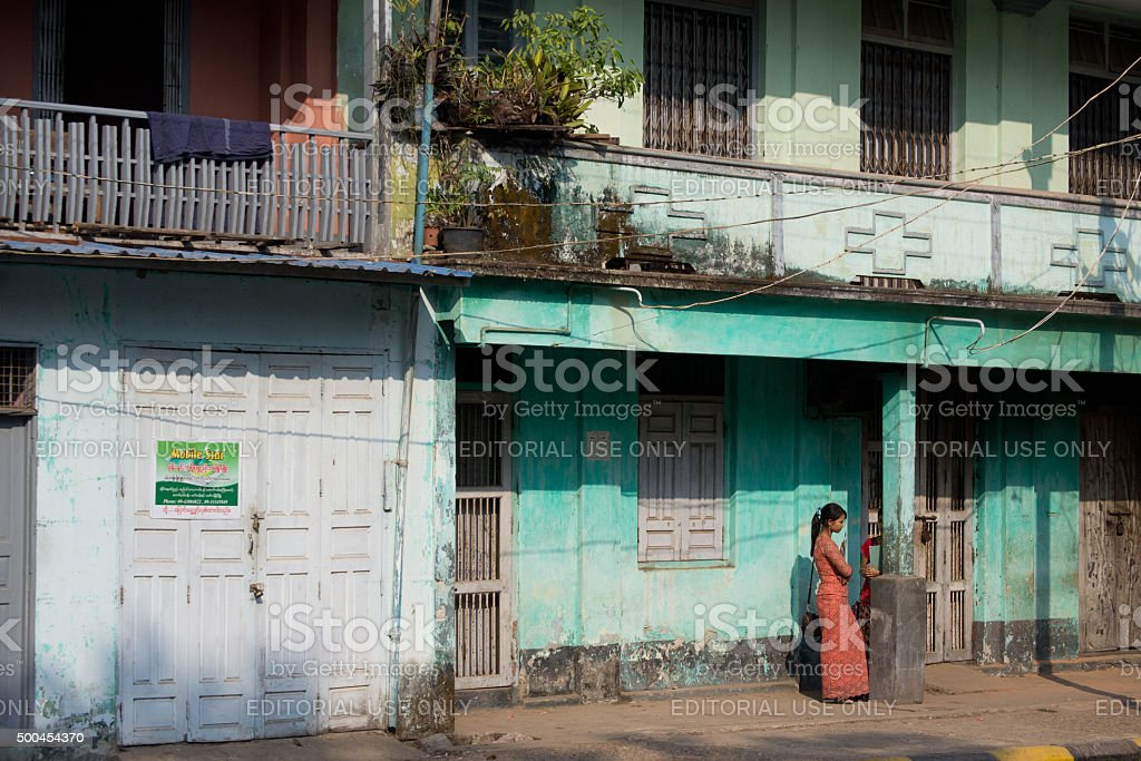 Burma, Myanmar. Mawlamyine. Colonial buildings with lady. stock photo
