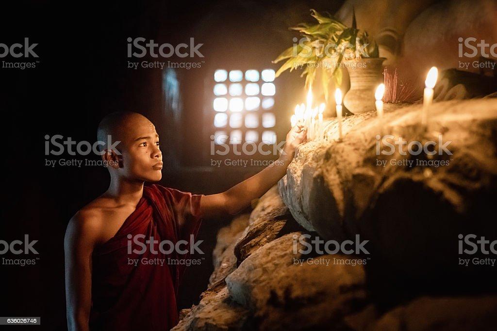 Burma Novice Monk Lighting Temple Candles to Worship Buddha Myanmar stock photo