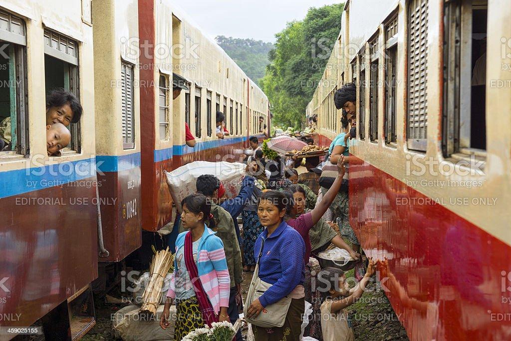 Burmese commuters between two passenger trains stock photo