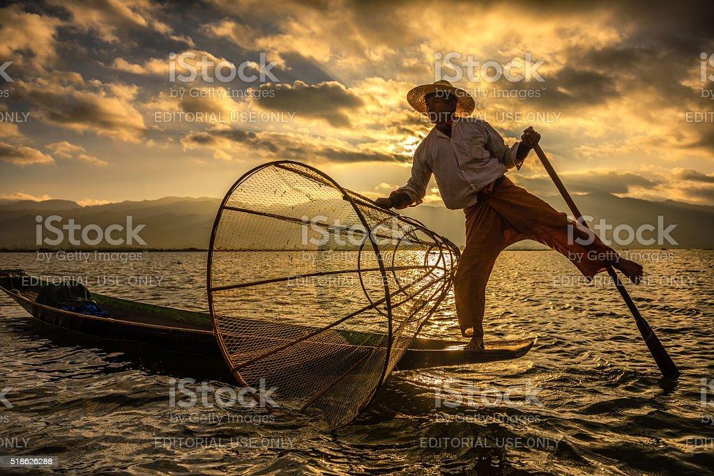 Burmese fisherman on a bamboo boat at sunrise stock photo