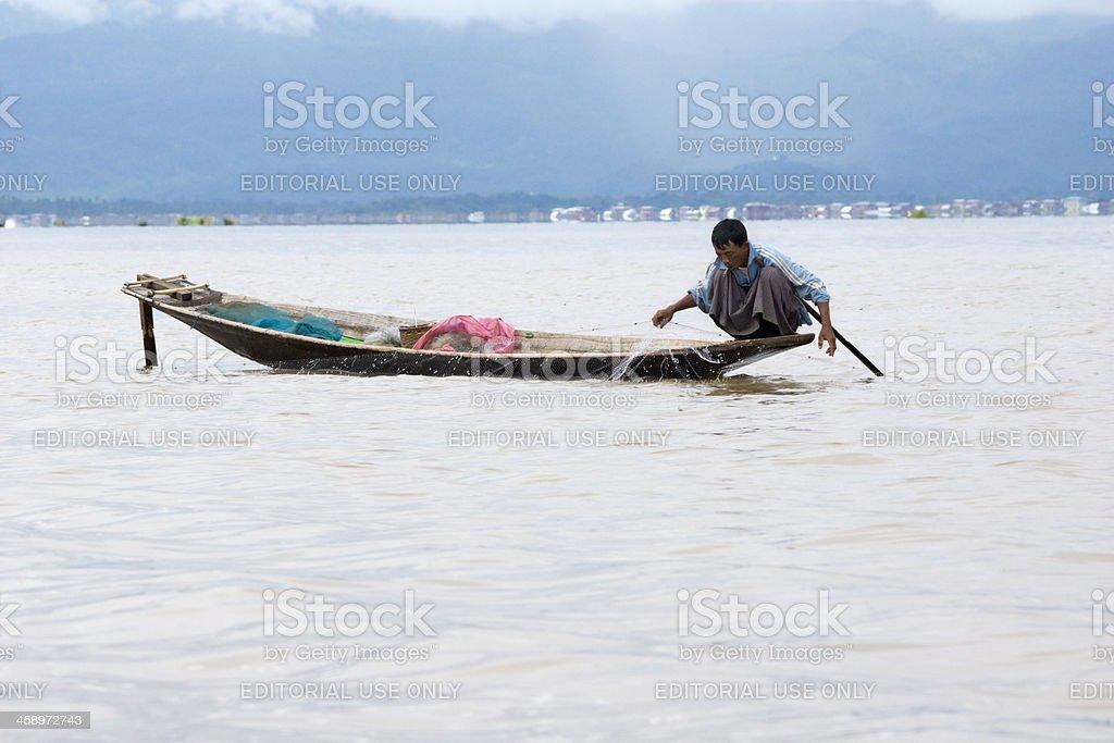 Burmese fisherman sitting in a canoe, Inle Lake stock photo