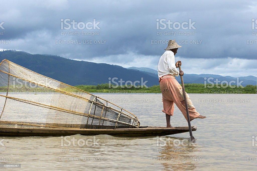 Burmese fisherman standing on a canoe, Inle Lake stock photo