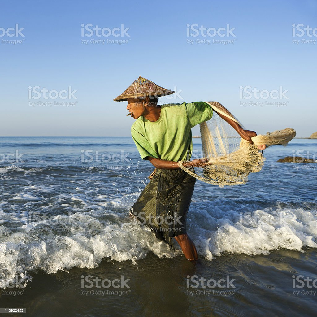 Burmese fisherman throwing a fishing net on Ngapali Beach royalty-free stock photo