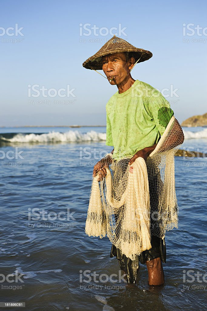 Burmese fisherman throwing a fishing net on Ngapali Beach royalty-free stock photo