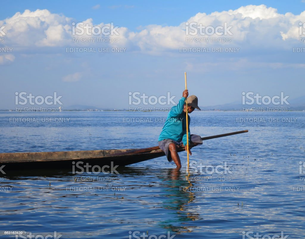 Inle Lake, MYANMAR - December 06, 2016: Burmese fisherman with a spear struck in the water, sitting down on his boat. 06 December, 2016 stock photo