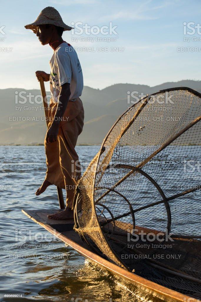 Burmese fishermen on boat with fishing net at Inle lake in Myanmar (Burma) stock photo