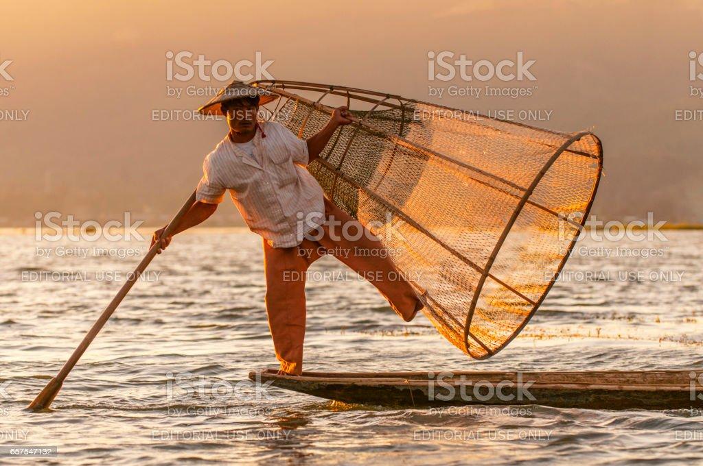 Burmese fishermen with fishing net at Inle lake in Myanmar. stock photo