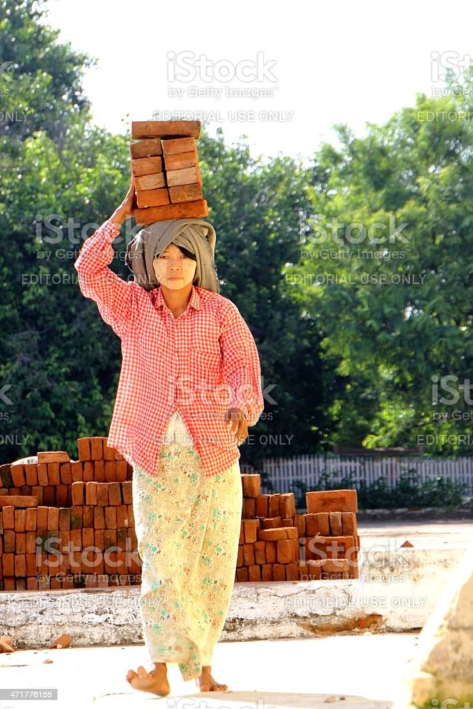 Burmese girl carrying bricks stock photo