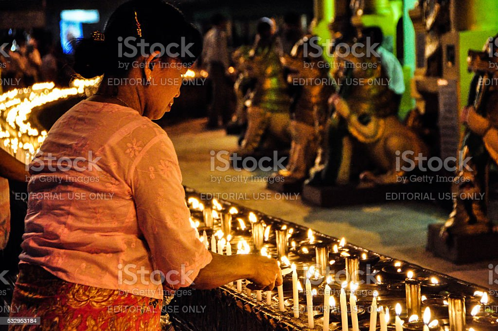 Burmese lady is lighting up the candle at dusk. stock photo