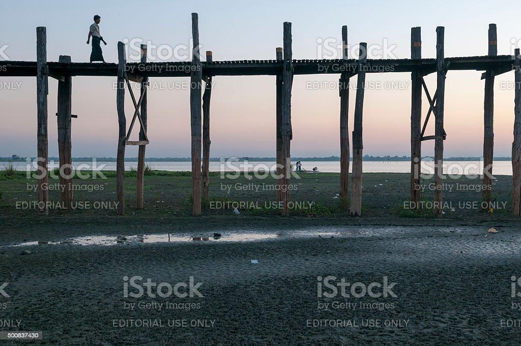 Burmese man walking on U Bein Bridge stock photo