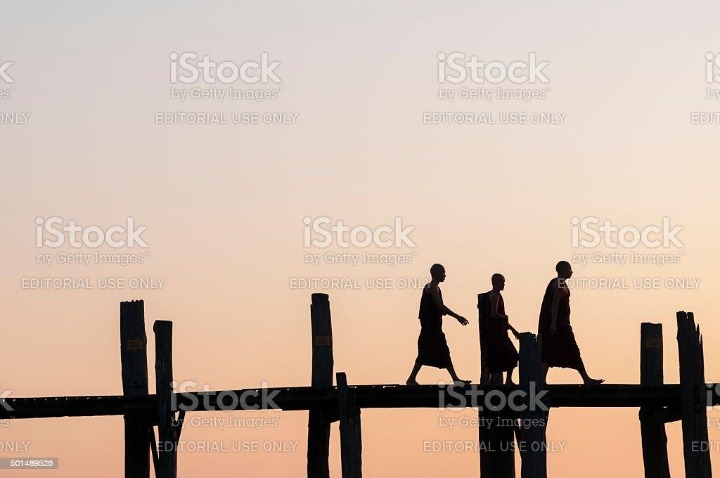 Burmese monks on U Bein Bridge stock photo