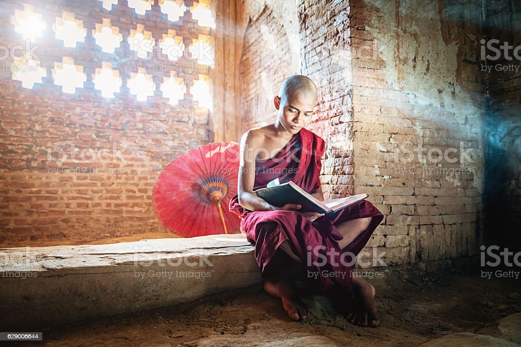 Burmese Novice Buddhist Monk in Temple Reading Bagan Myanmar stock photo