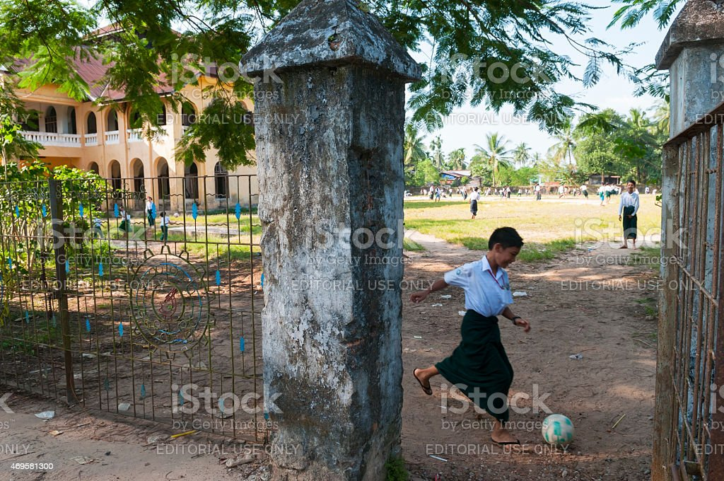 Burmese school children playing with soccer ball in Mawlamyine stock photo