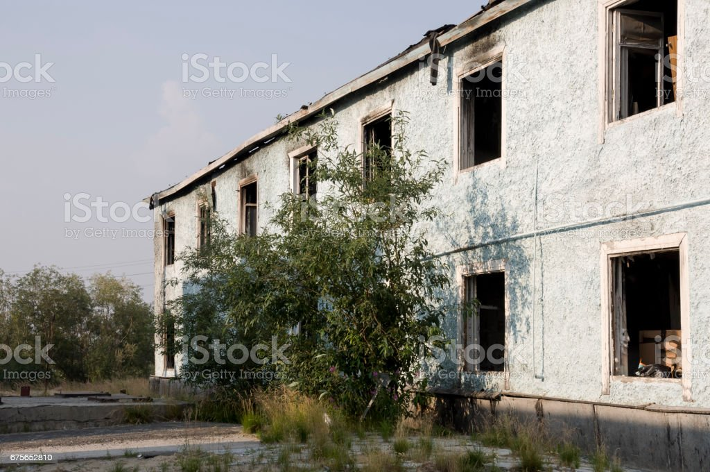Burnеd light blue two-storeyed building with green trees. After fire stock photo