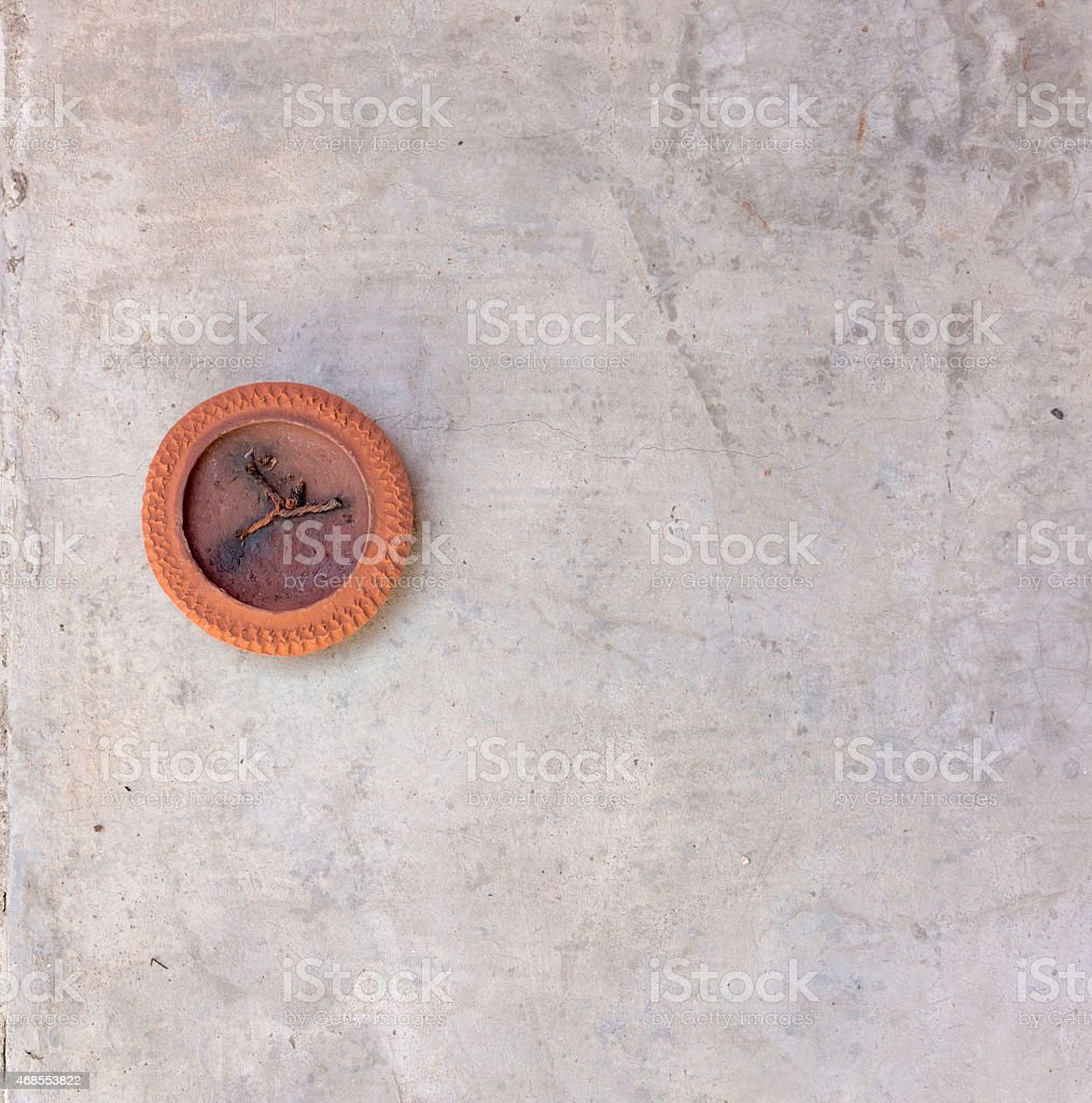 Burned clay candle on the gray cement wall royalty-free stock photo