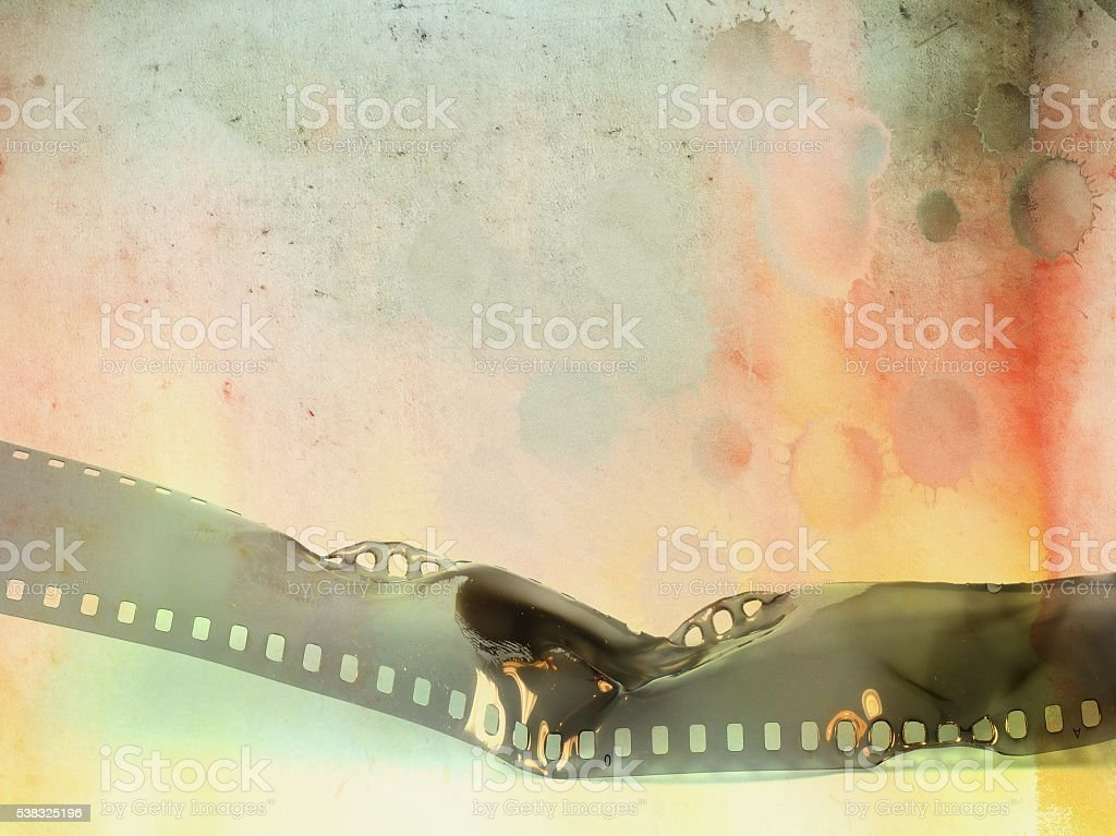 Burned film strip on stained paper background stock photo