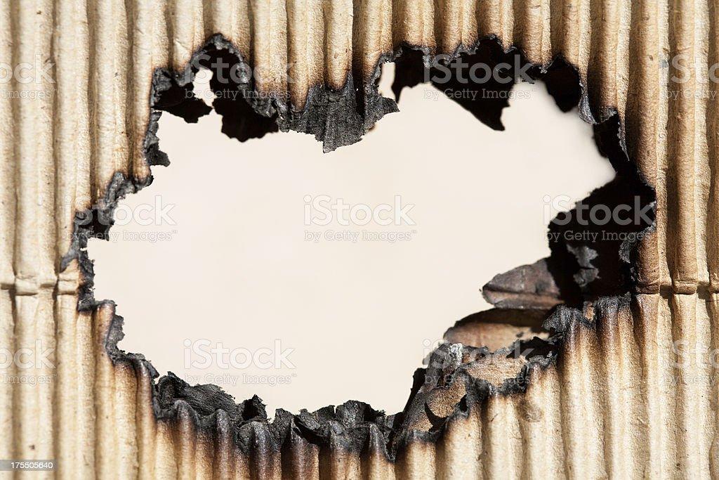 Burned hole in cardboard stock photo