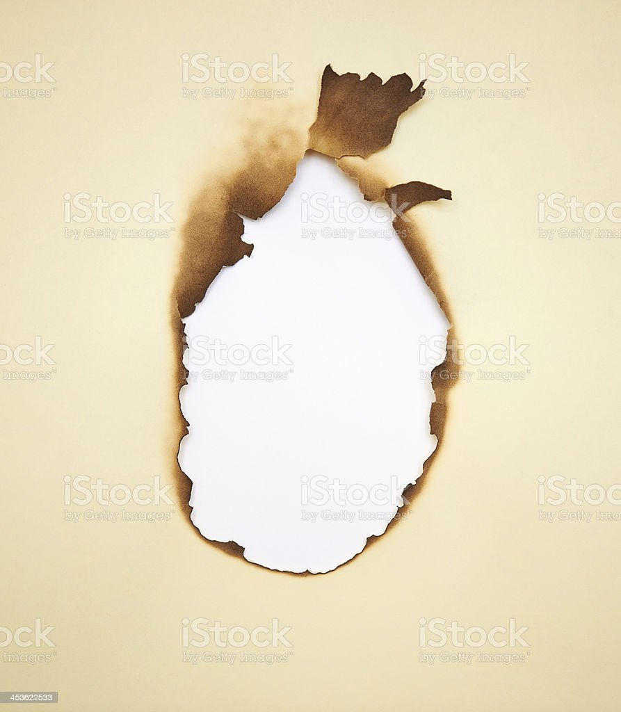 Burned hole within yellow paper. Grunge frame with scorched edge royalty-free stock photo