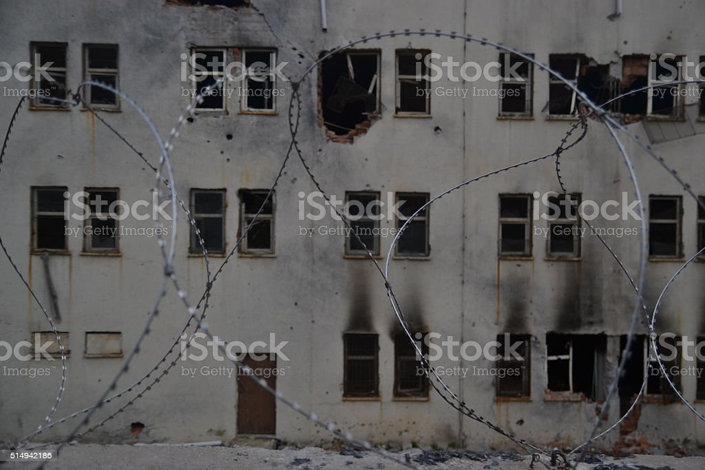 Burned House in ruins behind barbed wire. stock photo