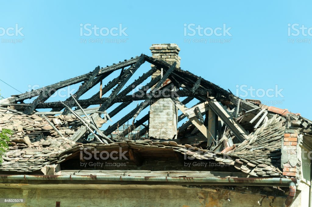 Burned roof of abandoned civilian house in Eastern Ukraine damaged by grenade explosion in the war zone stock photo