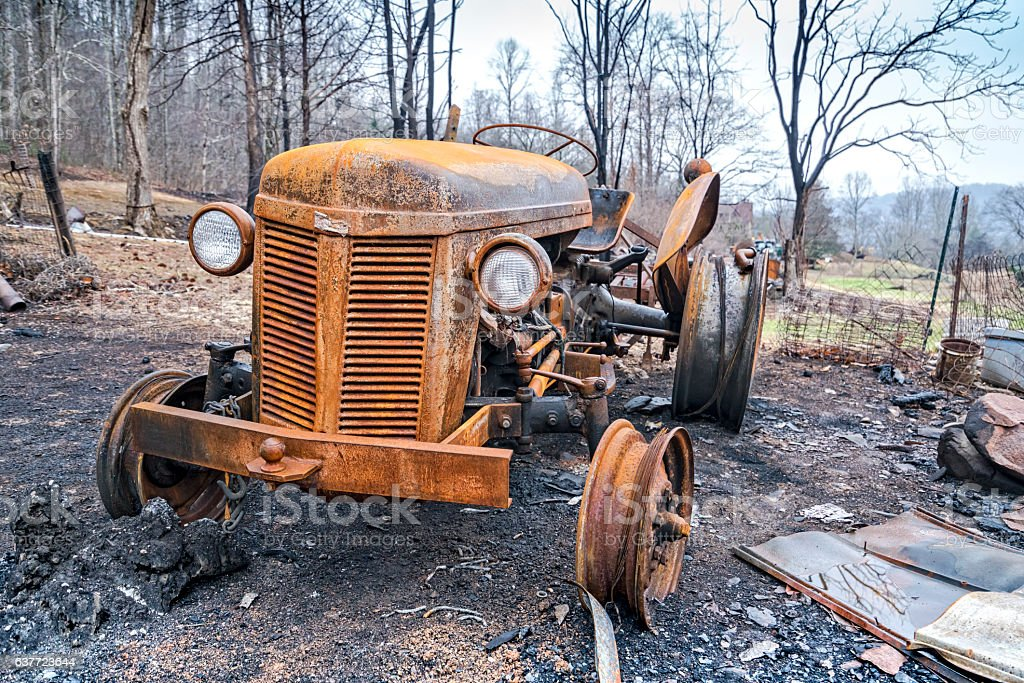 Burned tractor and car after forest fire stock photo