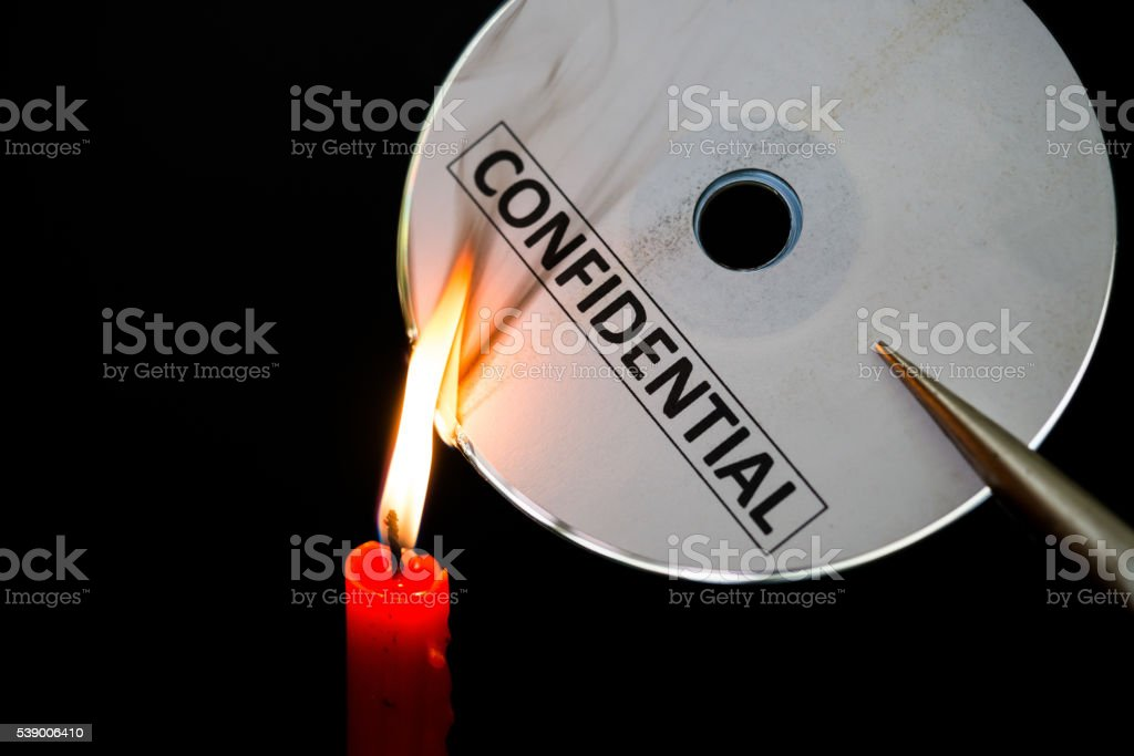 burning a confidential compact disc with candle in dark stock photo