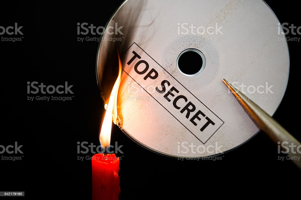 burning a top secret compact disc with candle in dark stock photo